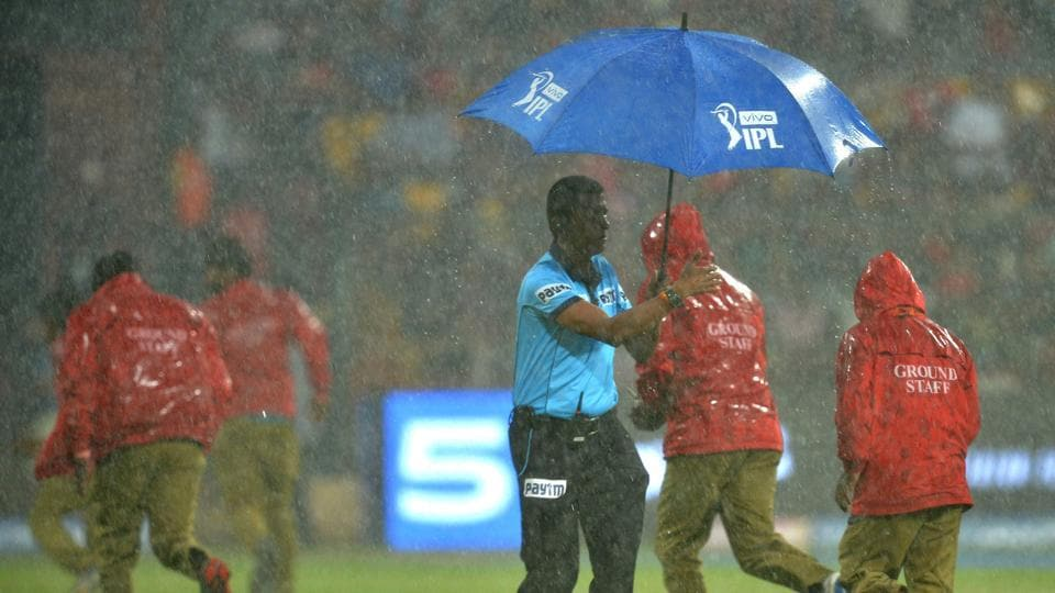 An umpire (C) and ground staff run for cover as rain delays the start of the 2019 Indian Premier League (IPL. (AFP)