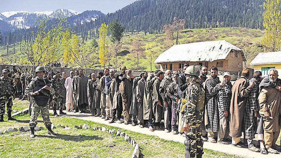Security personnel stand guard as voters wait in queue to cast their votes outside a polling station at Gulzarabad in Kulgam district on April 29.