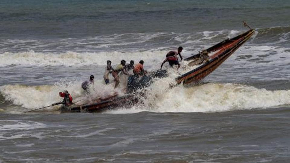 Fishermen try to control their boat amidst rough sea waters at Puri beach, Tuesday, April 30 2019.