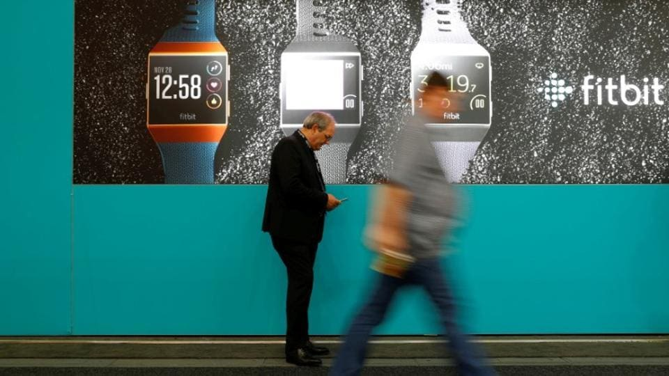 Visitors walk past an advertising billboard for Fitbit Ionic watches at the IFA Electronics Show in Berlin, Germany, September 1, 2017.