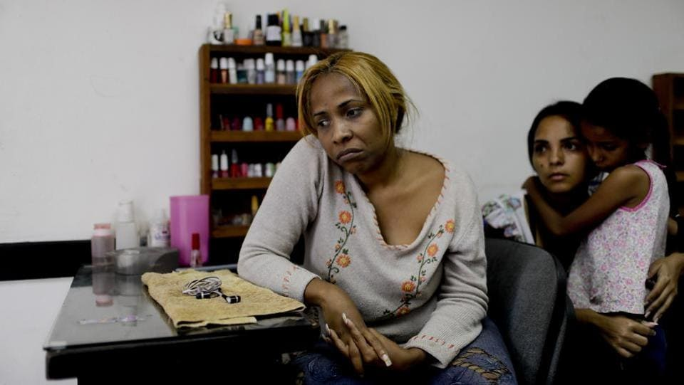 Manicurist Maria Trinidad Tobar waits for customers at a beauty salon in Caracas. Tobar said Venezuelan women no longer prioritize getting made up, but instead focus on buying food in a country where the IMF predicts hyperinflation will reach 10,000,000% this year. (Natacha Pisarenko / AP)