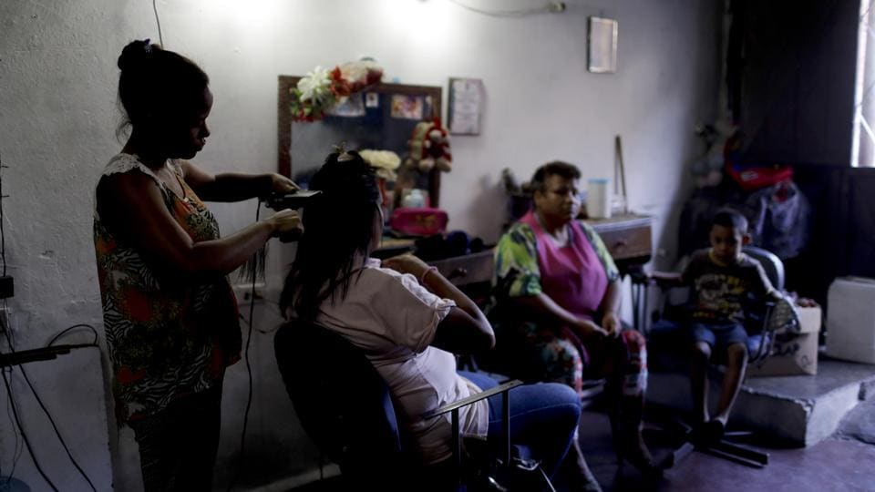 Hair dresser Rosevel Velazquez attends a customer at her beauty salon, which she runs out of her home in Caracas. Some salon workers have started bartering hair stylings, manicures and pedicures for food at a time when Venezuela's sharp economic decline has led to shortages of food and medicine, and made salaries nearly worthless. (Natacha Pisarenko / AP)