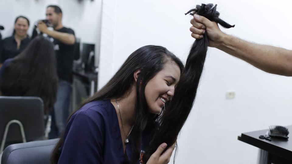 "Valery Diaz holds the hair she had cut off. Despite sacrificing her hair, Diaz said she still tries to buy cosmetics, using money she earns from making and selling bracelets. Diaz said she still dreams of becoming a Miss Venezuela someday, when ""my hair grows again."" (Natacha Pisarenko / AP)"