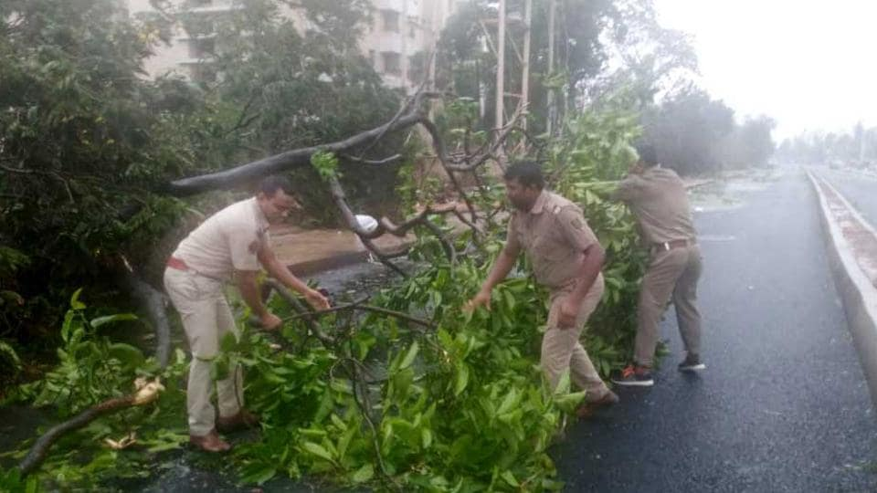 Police personnel of Nayapalli police station clear roads in Bhubaneswar on Friday. Several trees have been uprooted in the heavy rain and strong winds due to cyclone Fani which hit the region.