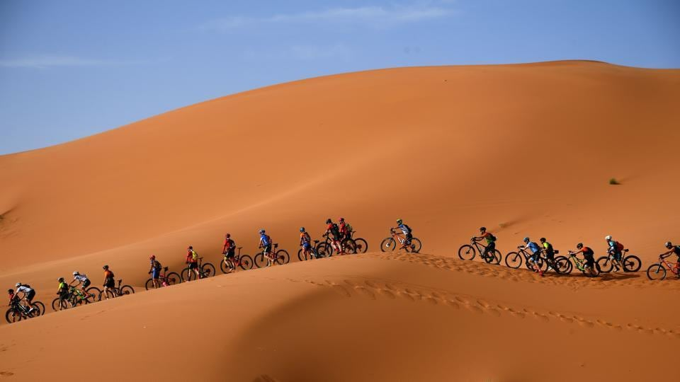 Competitors ride their bikes along sand dunes during Stage 1 of the 14th edition of Titan Desert 2019 mountain biking race around Merzouga in Morocco. (Franck Fife / AFP)
