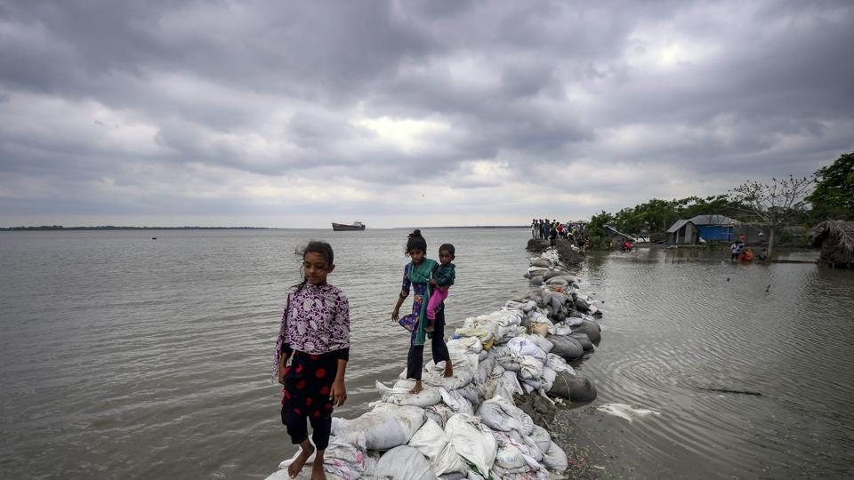 Bangladeshi children walk on top of a sandbag embankment that was breached by high waters in Khulna as cyclone Fani reached Bangladesh. At least 12 have been killed across Bangladesh due to the cyclonic storm Fani, which is expected to stay over the country until 4 pm today, according to a news report. (Munir Uz Zaman/ AFP)