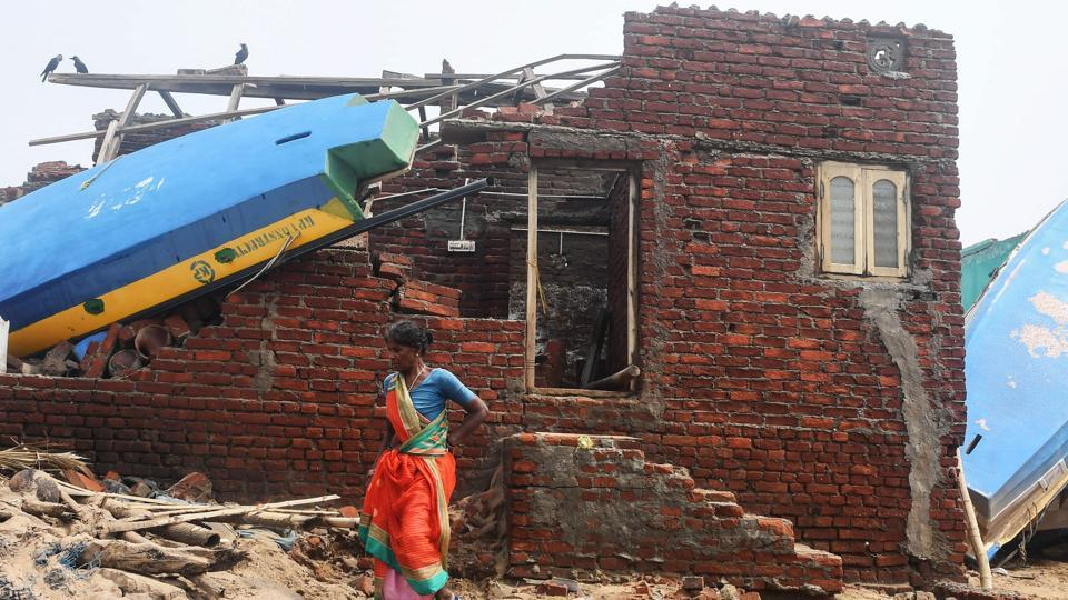 An Indian woman walks next to a damaged building with a fishing boat lodged on its roof along the seafront in Puri in the eastern Indian state of Odisha on May 4, 2019, after Cyclone Fani swept through the area.