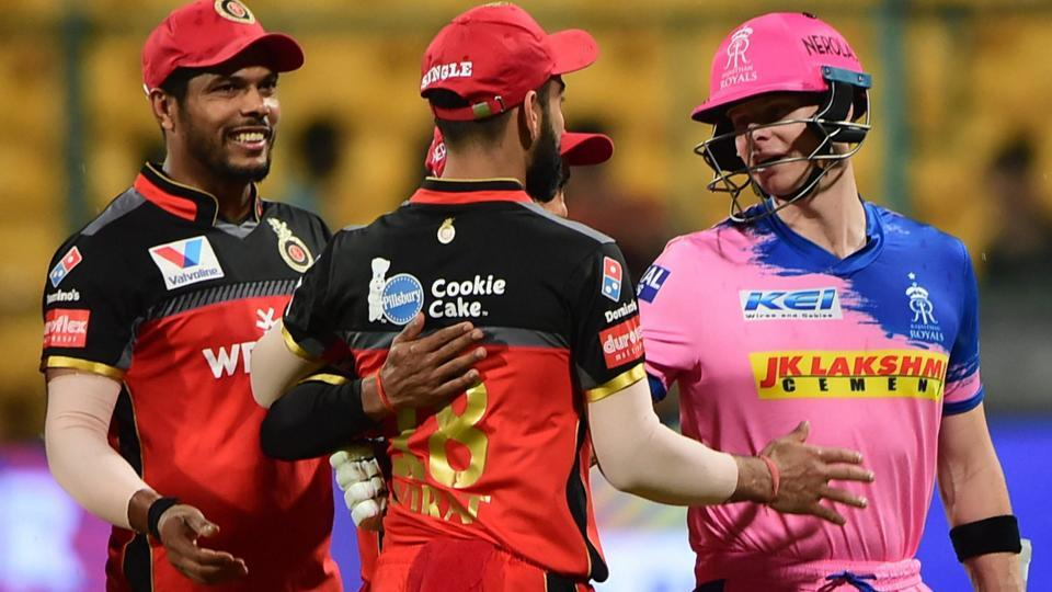 RR. Batsman Steve Smith shakes hand with RCB Skipper Virat Kohli after the match was called off due to rain .