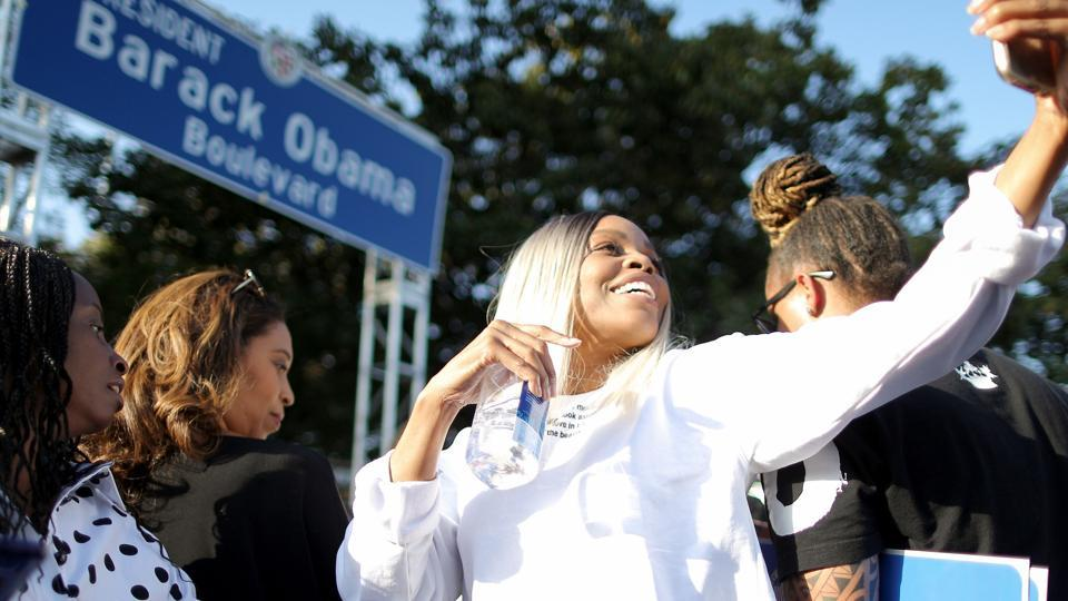 A woman takes a selfie in front of the unveiled street sign, at a festival where a South Los Angeles street was renamed Obama Boulevard, in honor of former US President Barack Obama, on May 4, 2019 in Los Angeles, California.