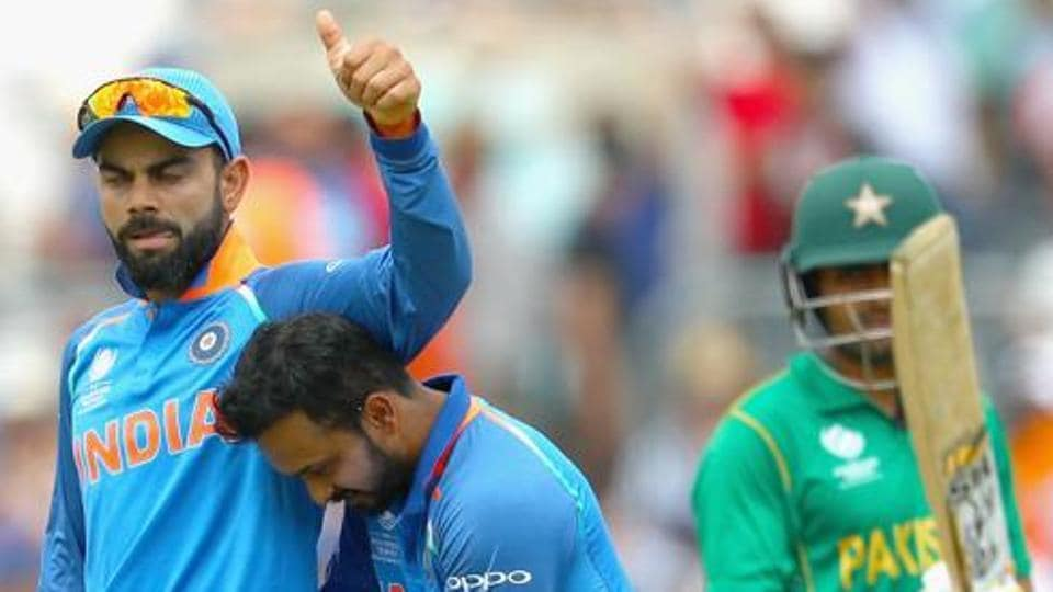 Kedar Jadhav of India celebrates the wicket of Babar Azam of Pakistan with Virat Kohli.