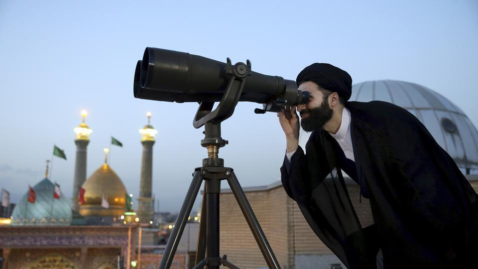 A cleric looks through binoculars to spot the new moon that signals the start of the Islamic holy fasting month of Ramzan, at the shrine of the Shiite Saint Imam Abdulazim in Shahr-e-Ray, Iran. Some prefer the many advances in technology for predicting the sighting; others would rather stick to tradition, relying on the naked eye. (Ebrahim Noroozi / AP)