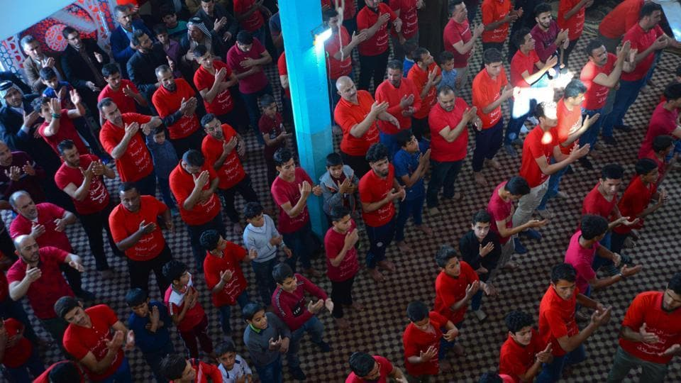 Teens in matching red shirts stand shoulder to shoulder in their local place of worship as if preparing for prayer and the ear-splitting drums reverberate around the hall as Iraqi teenagers shout rhymes venerating the Prophet Mohammad's grandson and other honoured figures in Islam.   (Haidar Hamdani / AFP)