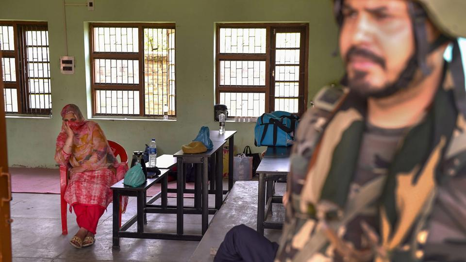 A security personnel stands guard as poll officials wait for voters at a polling station in Anantnag district of Jammu and Kashmir on April 23.
