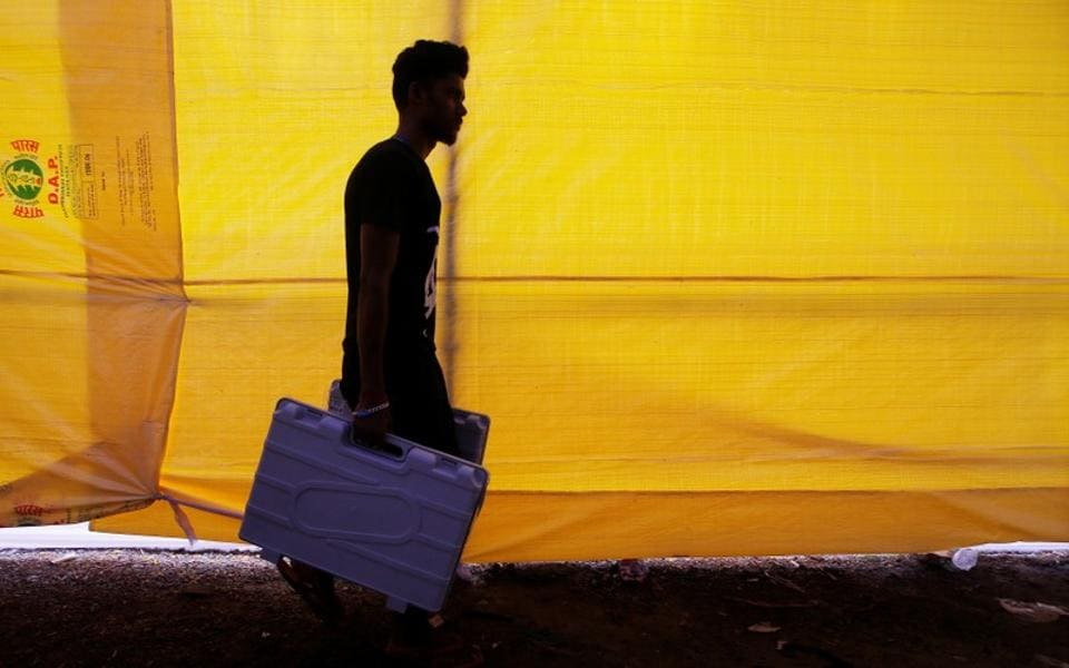 An election staff member carries Electronic Voting Machines (EVM) after collecting them from a distribution centre.