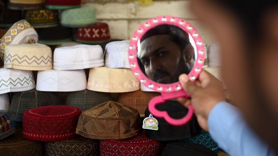 A Pakistani Muslim tries on a traditional prayer cap along a roadside shop in preparation for the Muslim fasting month of Ramzan in Karachi. (Rizwan Tabussum / AFP)