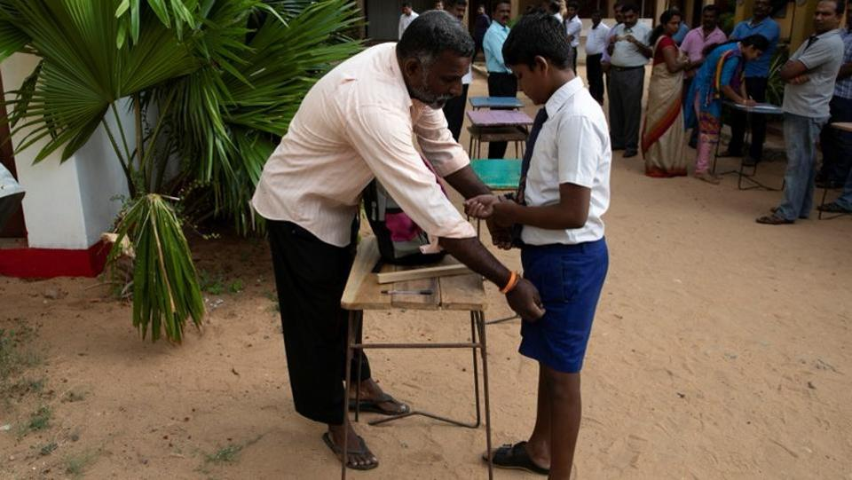 A student is frisked by a parent as he arrives at his school in Batticaloa. Despite the tight security and military patrols, most classrooms were near empty on Monday. Private schools, including Catholic institutions, remained closed. (Danish Siddiqui / REUTERS)