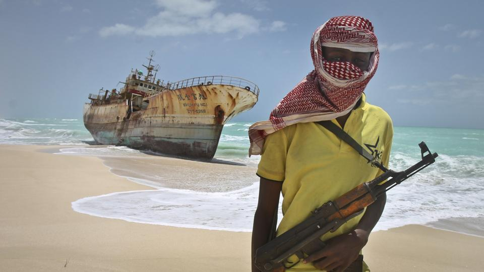 In this file photo,a  masked Somali pirate stands near a Taiwanese fishing vessel that washed up on shore after the pirates were paid a ransom and released the crew, in the once-bustling pirate den of Hobyo, Somalia.