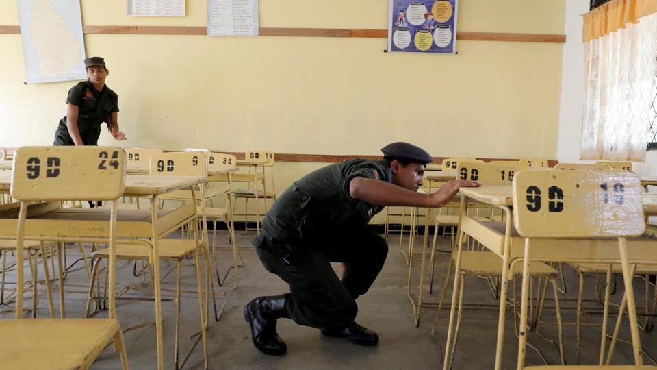 Sri Lankan army soldiers search a class room. At Royal College, an elite state school in Colombo, the parking area usually filled with school vans on a normal day was practically empty. Only about 5% of its 6000 students were back in classes, a school official said. (Dinuka Liyanawatte / REUTERS)
