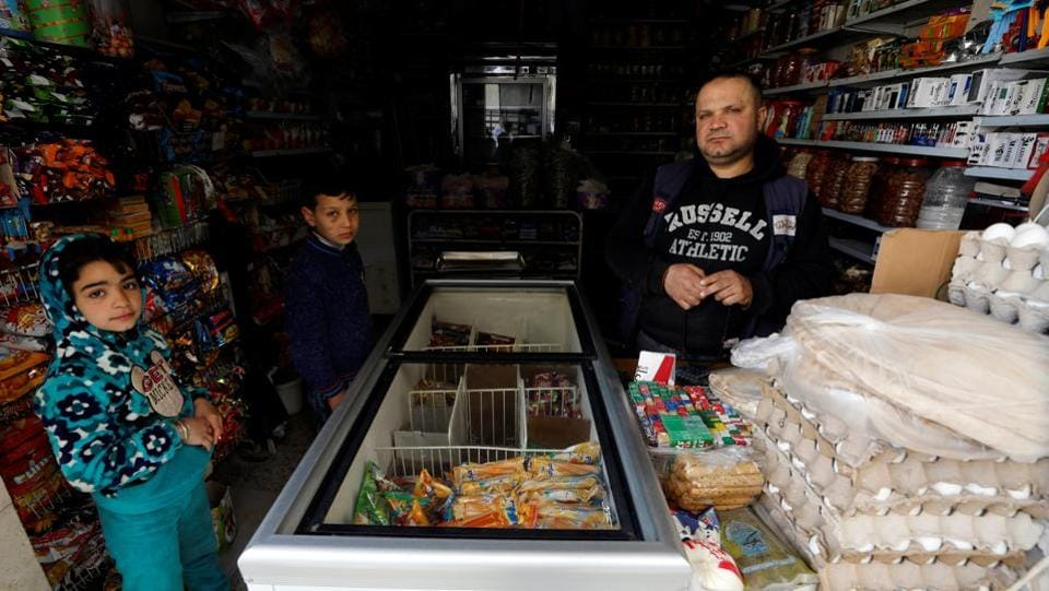 Behind one street of entirely collapsed buildings is a mechanic's garage where workers are elbow deep in the engine of Karim's taxi. Across the main street, the al-Burr family lives down another side street. Hussein (R), 41, minds the grocery shop, selling tins and packets of food, eggs and sweets. (Omar Sanadiki / REUTERS)