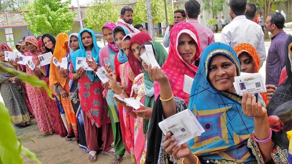 Woman Voters shows their voter id cards as they stand in queue to cast their votes at polling station during the 5th phase of Lok Sabha elections in Rajasthan.