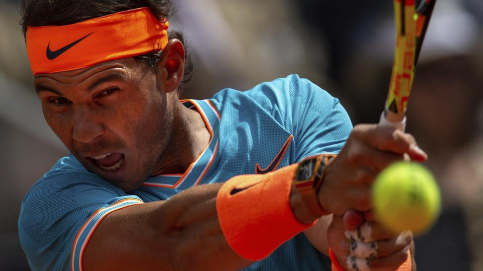 Rafael Nadal, from Spain, returns the ball to Felix Auger-Aliassime, from Canada.