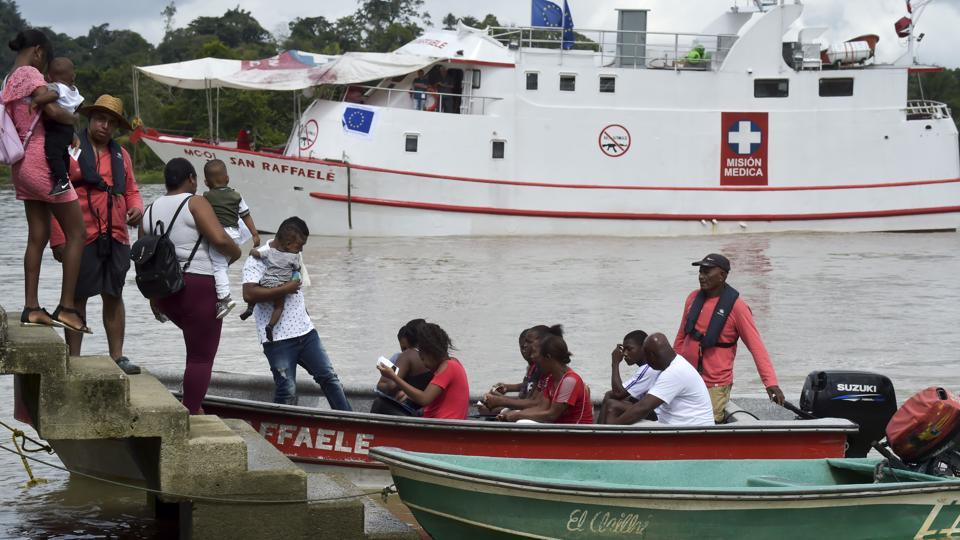 Locals get on a boat to the hospital ship San Raffaele, in Docordo municipality, on the banks of San Juan river, Colombia. The hospital ship