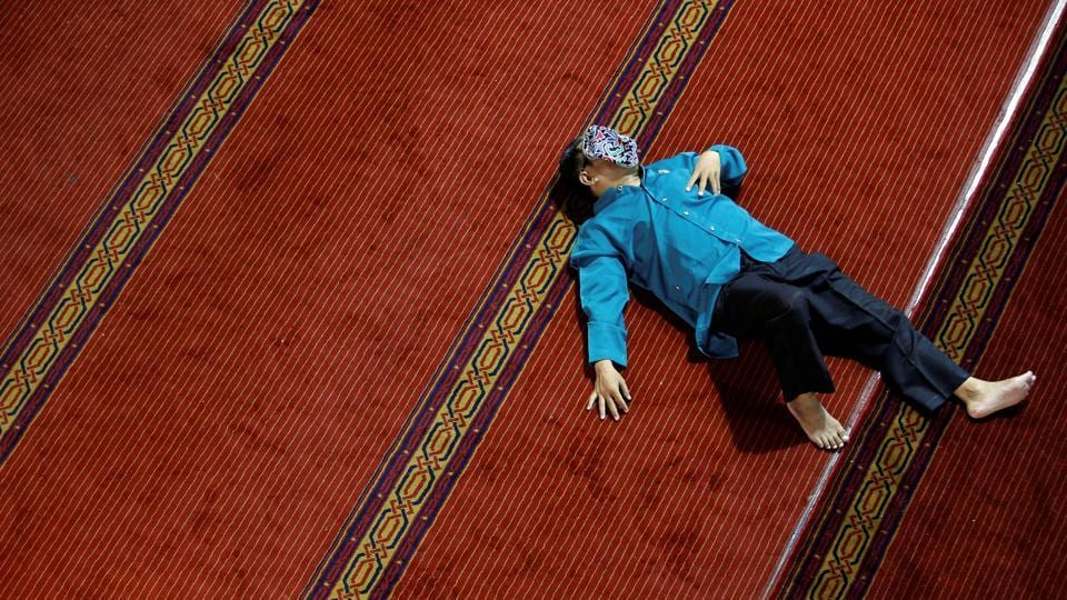 A man takes a rest as he waits for iftar, the breaking of the fast, during the holy month of Ramadan at Istiqlal mosque in Jakarta, Indonesia. (Willy Kurniawan / REUTERS)