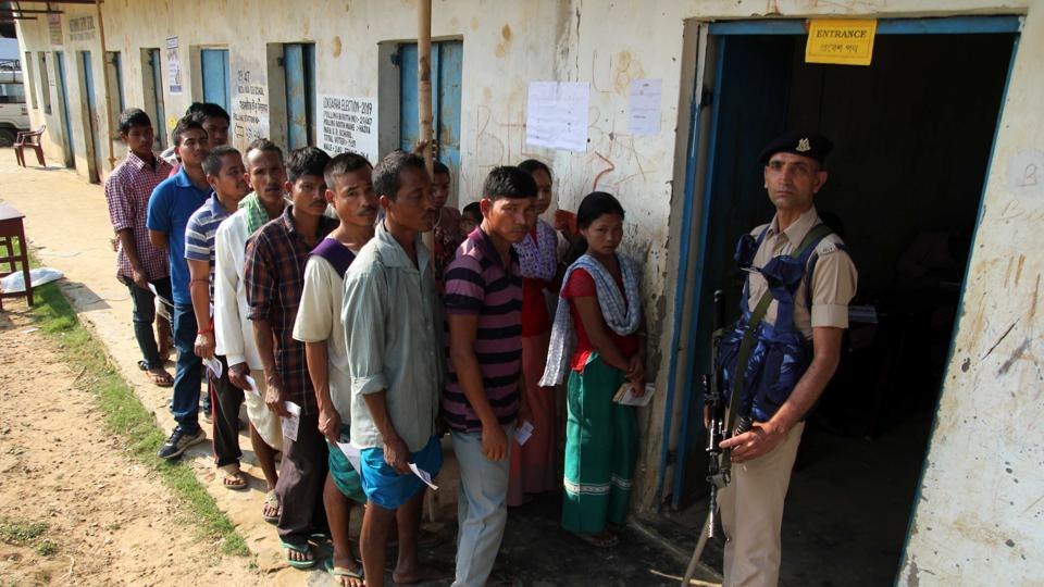 Tripura, April 23 (ANI): A CRPF officer stands guard at the polling station as the voters in a queue to cast vote during the general election at village Hajaripara in Agartala on Tuesday. (ANI Photo)