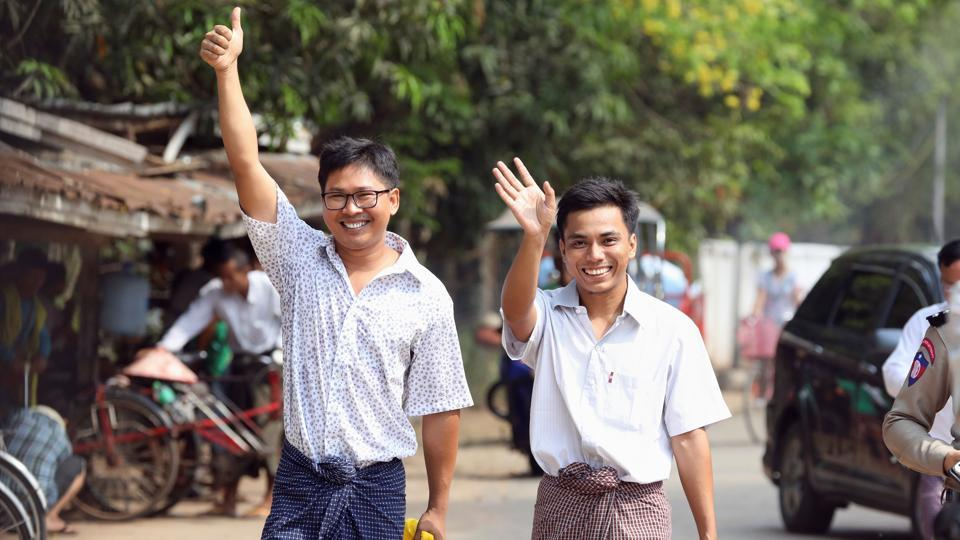 Reuters reporters Wa Lone and Kyaw Soe Oo gesture as they walk to Insein prison gate after being freed, after receiving a presidential pardon in Yangon, Myanmar. (Ann Wang / REUTERS)
