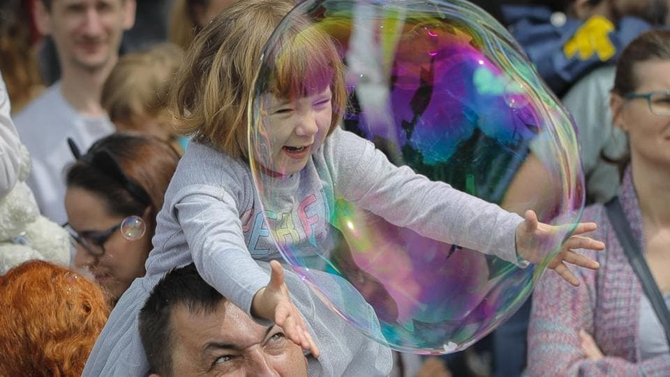 A child reaches for a soap bubble during the Global Bubble Parade in Bucharest, Romania. (Vadim Ghirda / AP)