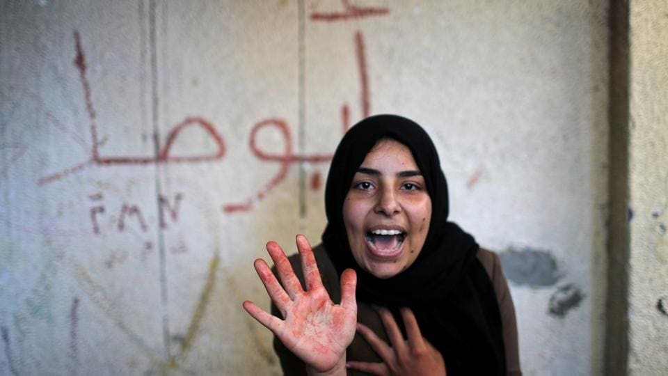 The sister of 22-year-old Palestinian Emad Naseer, who was killed in an Israeli air strike, reacts with her hand stained with his blood, during his funeral in the northern Gaza Strip. (Mohammed Salem / REUTERS)