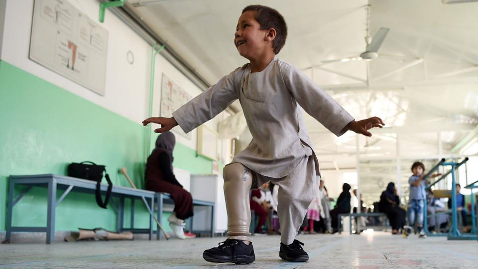 Ahmad Sayed Rahman, a five-year-old Afghan boy who lost his right leg when he was hit by a bullet in the crossfire of a battle, dances with his prosthetic leg at the International Committee of the Red Cross (ICRC) hospital for war victims and the disabled, in Kabul, Afghanistan. (Wakil Kohsar / AFP)
