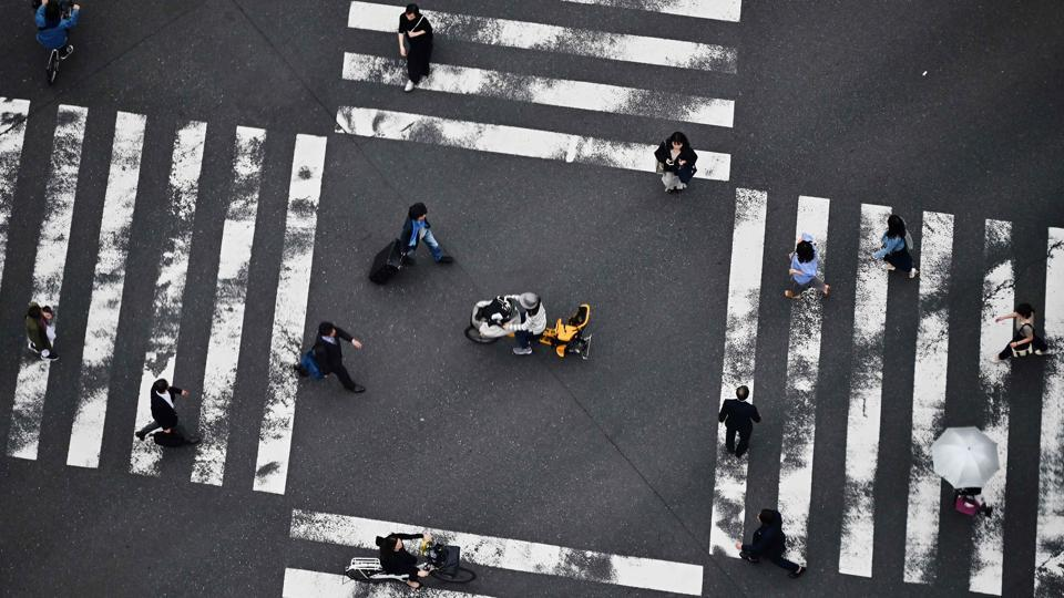 People cross a street in Tokyo's Ginza district in Japan. (Charly Triballeau / AFP)