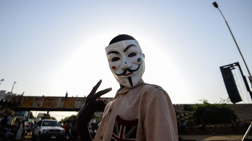 A Sudanese protester wears a Guy Fawkes mask outside the army headquarters in Khartoum, Sudan. (Mohamed el-Shahed / AFP)