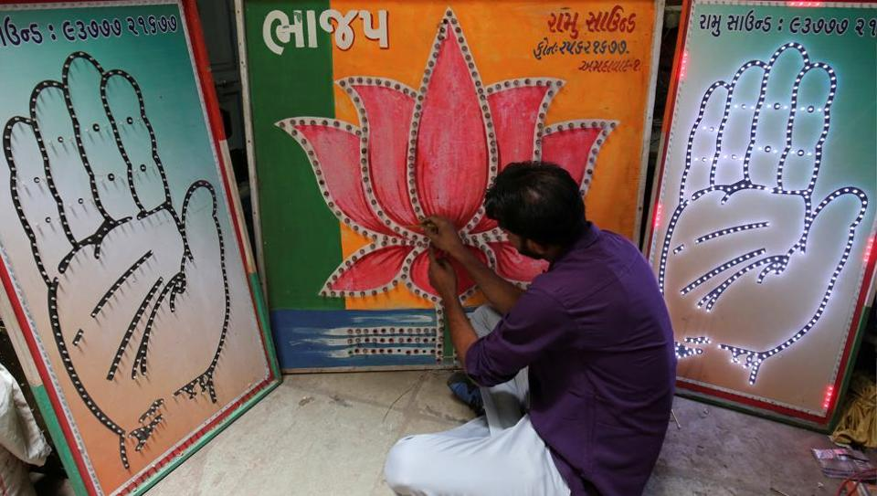 An electrician tests LED-light fitted boards with party symbols of  the Bharatiya Janata Party and the Congress