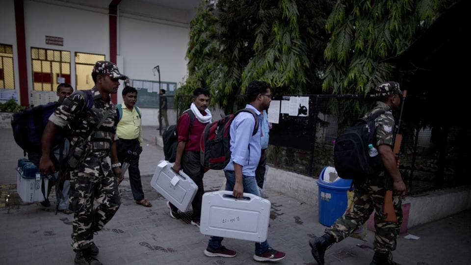 Election officers carry electronic voting machines at the end of polling in Prayagraj, Uttar Pradesh