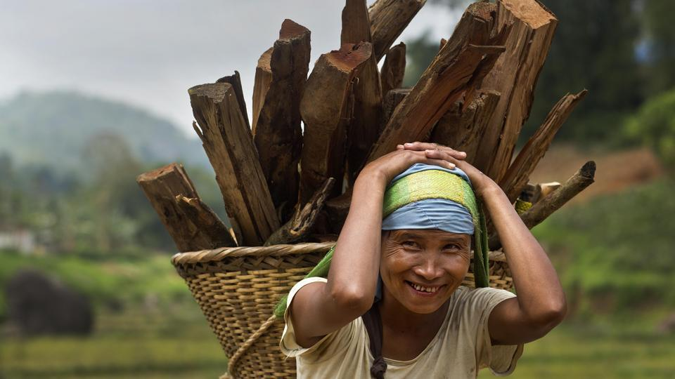 A Khasi tribal woman Lona Syngkli carries firewood in a basket swung around her head in Nongpoh, in Meghalaya state. As women, these voters already face immense hurdles in a nation where women are often relegated to second-class roles. Syngkli said she knew nothing about politics but had cast her vote because her husband told her to.  (Anupam Nath / AP)
