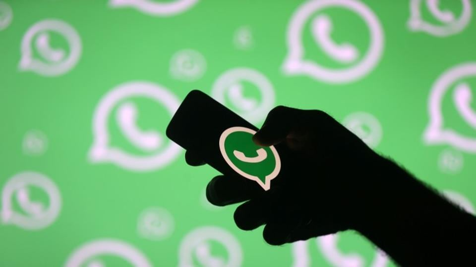 A man poses with a smartphone in front of displayed Whatsapp logo in this illustration September 14, 2017.