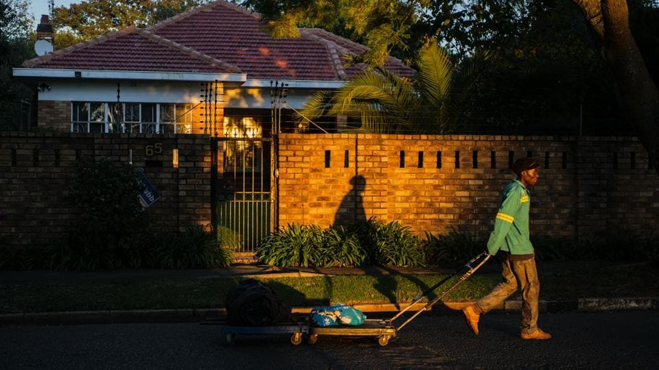 A waste-picker pulls a trolley of salvaged recyclable material along the road as the sun rises in a wealthy suburb of Johannesburg, South Africa. An estimated 6,000 waste-pickers in Johannesburg who live off other people's garbage in what the World Bank calls the most unequal country on earth. A legacy of apartheid, inequality remains so ingrained that the ruling African National Congress hasn't been able to narrow the wealth gap since taking power 25 years ago.  (Waldo Swiegers / Bloomberg)