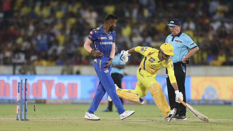 Chennai Super Kings captain Mahendra Singh Dhoni, center, runs unsuccessfully to make it to the crease.
