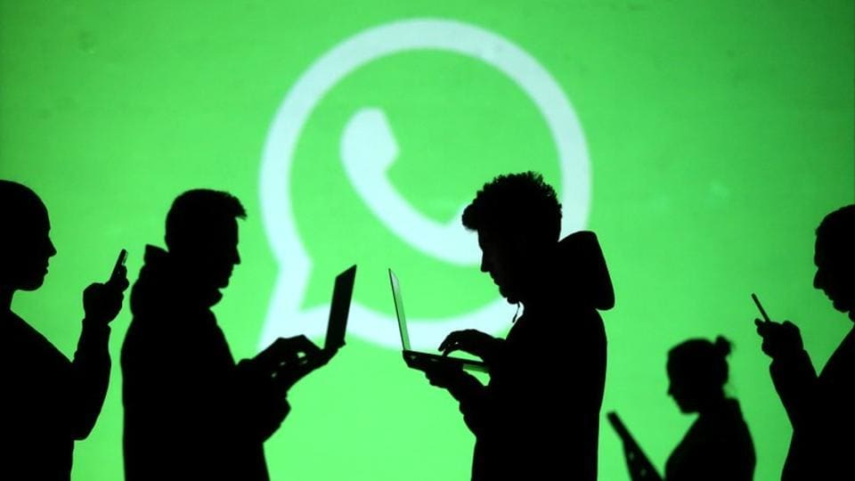 Silhouettes of laptop and mobile device users are seen next to a screen projection of Whatsapp logo in this picture illustration taken March 28, 2018.