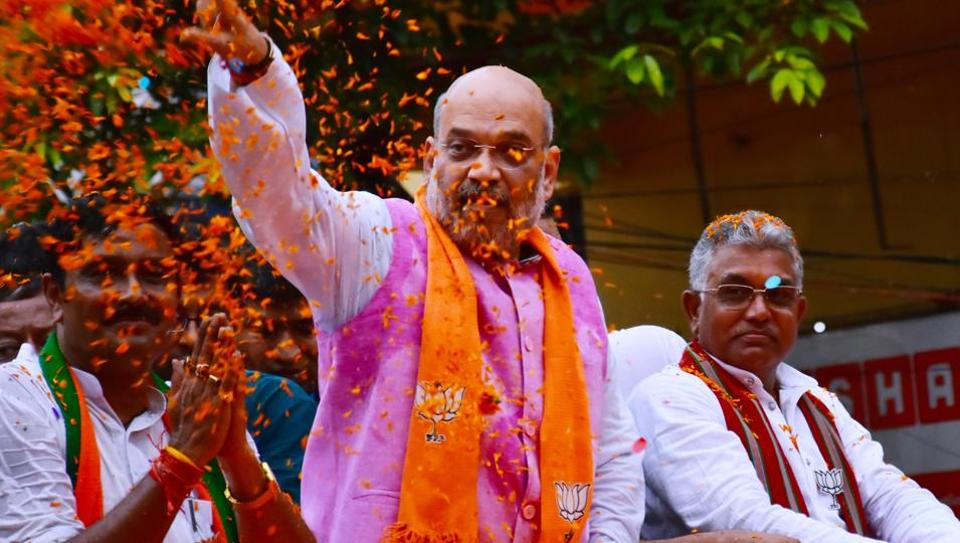 BJP president Amit Shah and  the party's Bengal unit chief Dilip Ghosh during a  road show in Kolkata on Tuesday.