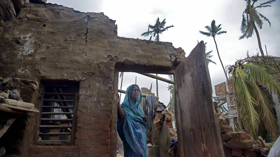 A woman stands in the remnants of her home in the aftermath of cyclone 'Fani', at the heritage crafts village Raghurajpur, in Puri district, Friday, May 10, 2019.