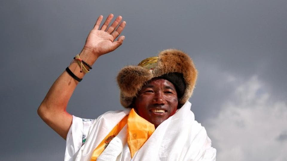 Kami Rita Sherpa, 48, a Nepali mountaineer waves towards the media personnel upon his arrival after climbing Mount Everest for a 22nd time, creating a new record for the most summits of the world's highest mountain, in Kathmandu, Nepal.