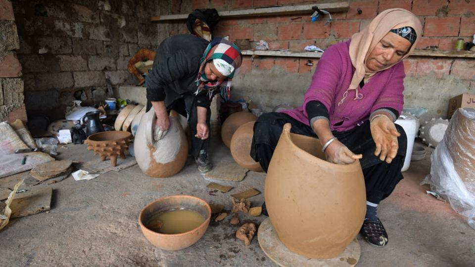 Seated in her lean-to overlooking the family lands, she scoops up the clay and spends most of her time fashioning utensils as well as stylised tortoises and horses. The women of Sejnane make and decorate their artisan pottery with natural elements from the agricultural region. (Fethi Belaid / AFP)