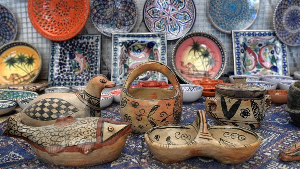 "Pottery crafted in Sejnane is displayed at a souvenir shop. Sejnane has plans to build a museum and training centre to preserve its local know-how. The pottery, mostly cream-coloured with black and red motifs, was added in 2018 to the prestigious ""Representative List of the Intangible Cultural Heritage of Humanity"" of UNESCO, the United Nations cultural organisation. (Fethi Belaid / AFP)"