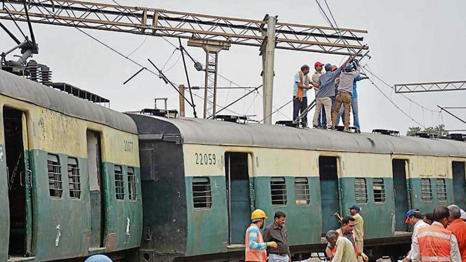 Members of the Accident Relief Staff in action as the second last coach of an EMU passenger train derailed in the morning, at Ghaziabad Railway Station, in Ghaziabad, India, on Thursday