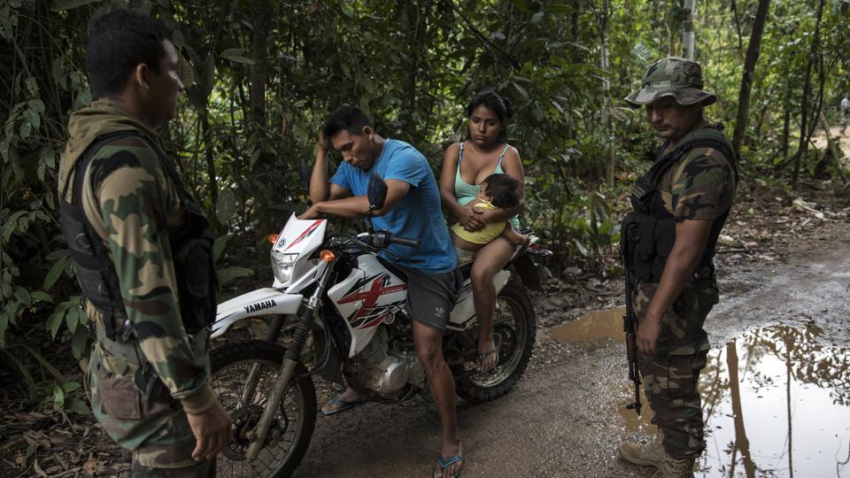 Policemen question a miner near the Mega 12 police base. They regularly patrol in vehicles and on motorcycles, though some miners emerge at night and there are concerns that others will wait for the military presence to subside, or simply relocate to more remote areas. (Rodrigo Abd / AP)