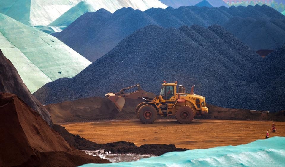 An excavator transfers imported iron ore at a port in Rizhao in China's eastern Shandong province. (AFP)