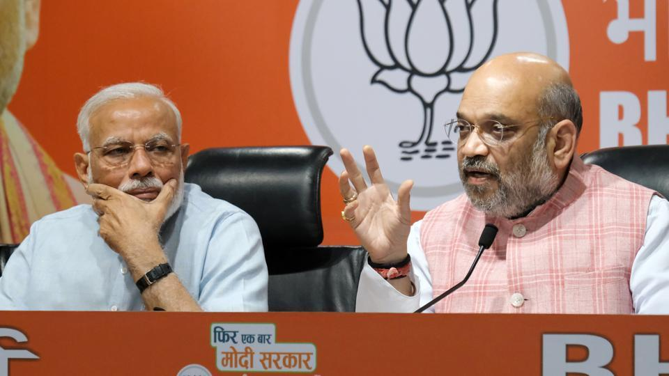 Amit Shah, president of Bharatiya Janata Party (BJP) speaks as Prime Minister Narendra Modi (L) watches him during a news conference at the BJP headquarters in New Delhi. (T. Narayan / Bloomberg)